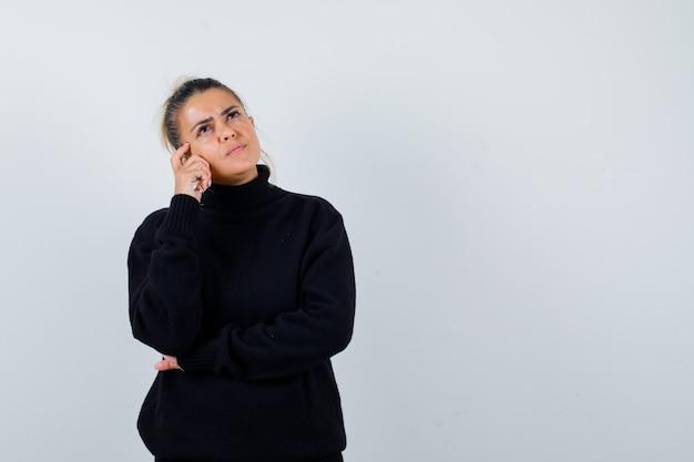 Jonge vrouw staande in denken pose in zwarte coltrui en peinzend, vooraanzicht op zoek.