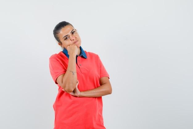 Jonge vrouw staande in denken pose, leunende wang aan kant in rode t-shirt en ziet er mooi uit. vooraanzicht.