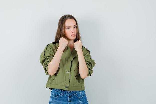 Jonge vrouw staande in strijd pose in jas, korte broek en op zoek zelfverzekerd. vooraanzicht.
