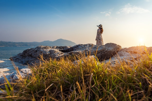 Jonge vrouw staande op de top van de rots bij zonsondergang in si chang island.