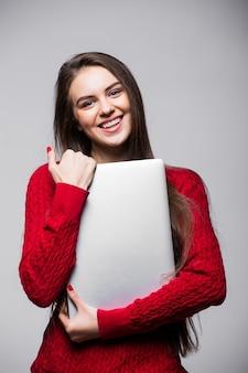 Jonge vrouw staande te houden laptop. gelukkig jong meisje met behulp van haar laptop, geïsoleerd op een witte muur.