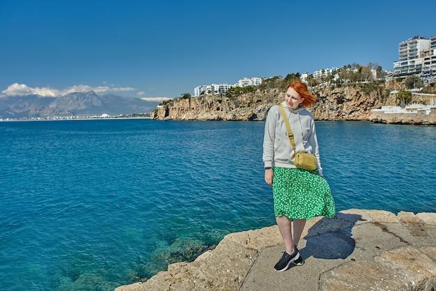 Jonge vrouw staat aan de kust van de zee.