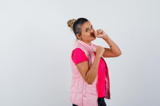 Jonge vrouw staat in bokser pose in roze t-shirt en jas en ziet er gelukkig uit