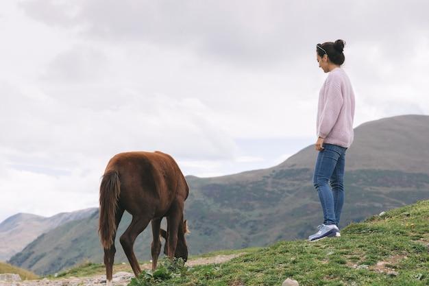 Jonge vrouw staat in de buurt van het paard op de achtergrond van de kaukasische bergen, georgië