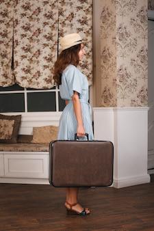 Jonge vrouw staat in de kamer met koffer. vintage reizen wachten concept.