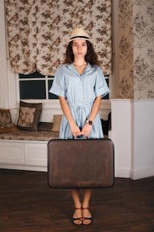 Jonge vrouw staat in de kamer met koffer.