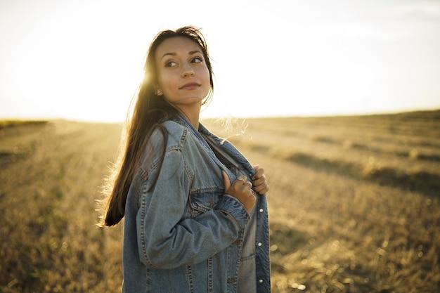 Jonge vrouw staat in de velden bij zonsondergang