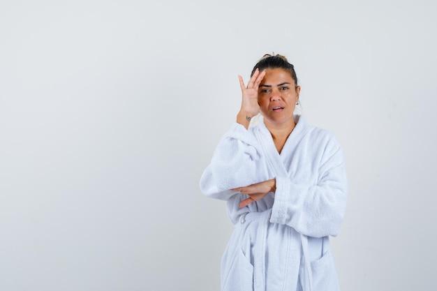 Jonge vrouw staat in denkende pose in badjas en kijkt peinzend