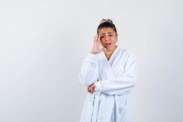 Jonge vrouw staat in denkende pose in badjas en ziet er vergeetachtig uit