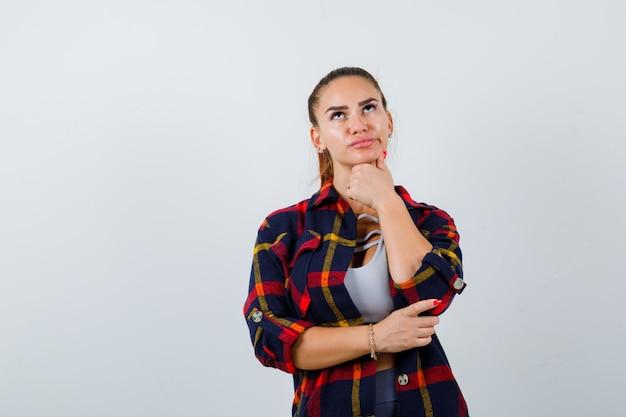 Jonge vrouw staat in denkende pose in crop top, geruit hemd en kijkt peinzend, vooraanzicht.