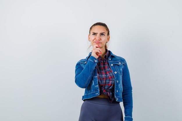 Jonge vrouw staat in denkende pose in geruit hemd, jas, broek en kijkt peinzend. vooraanzicht.