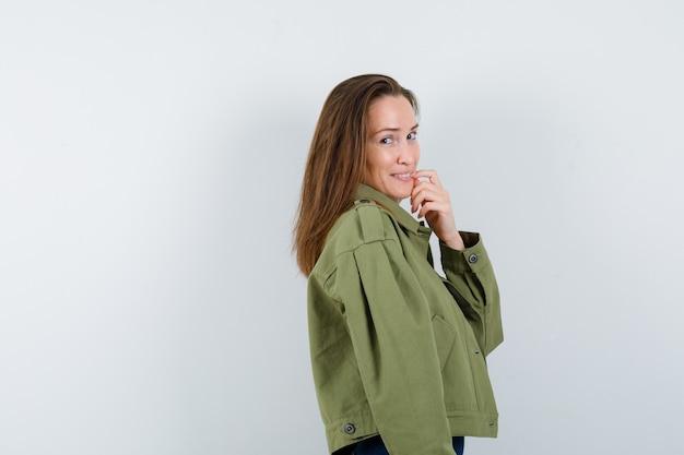 Jonge vrouw staat in denkende pose in jas en ziet er gracieus uit.