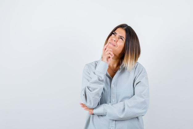 Jonge vrouw staat in denkende pose in oversized shirt en kijkt peinzend. vooraanzicht.