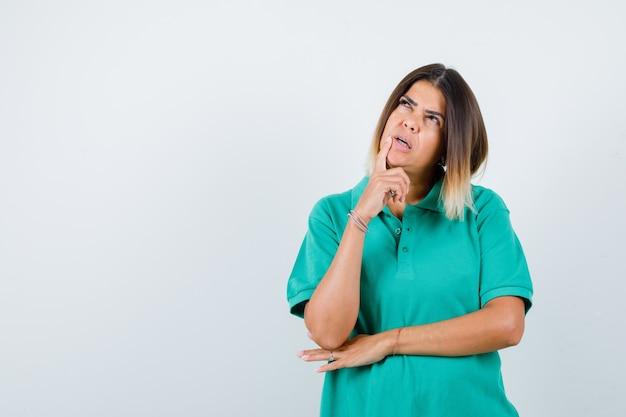 Jonge vrouw staat in denkende pose in polot-shirt en kijkt verbaasd, vooraanzicht.