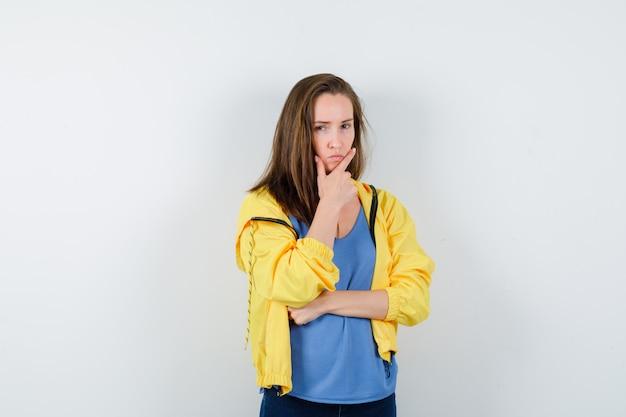 Jonge vrouw staat in denkende pose in t-shirt, jas en ziet er serieus uit, vooraanzicht.