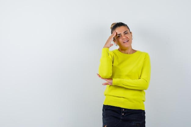 Jonge vrouw staat in denkende pose in trui, spijkerrok en ziet er attent uit