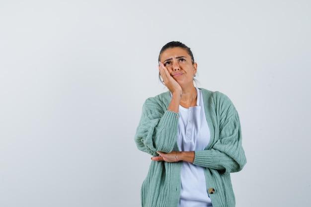 Jonge vrouw staat in denkende pose in wit overhemd en mintgroen vest en kijkt peinzend