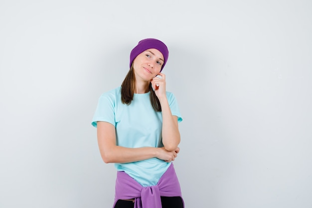 Jonge vrouw staat in denkende pose, leunt op de wang in blauw t-shirt, paarse muts en kijkt peinzend, vooraanzicht.