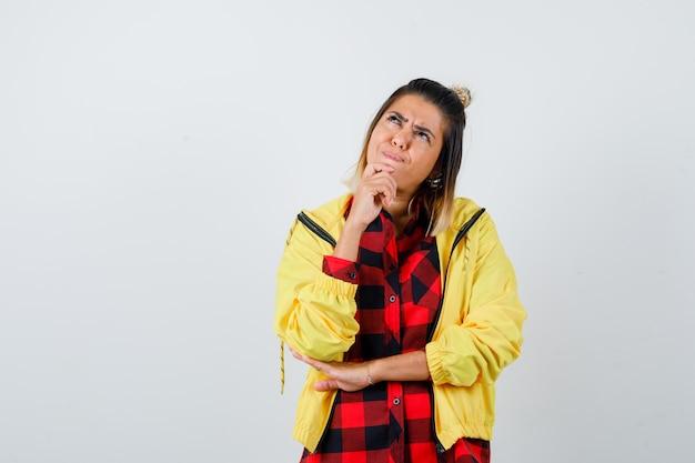 Jonge vrouw staat in denkende pose terwijl ze opkijkt in geruit hemd, jas en verbaasd kijkt, vooraanzicht.