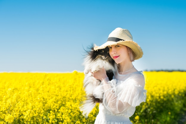 Jonge vrouw staat in een geel veld met hond