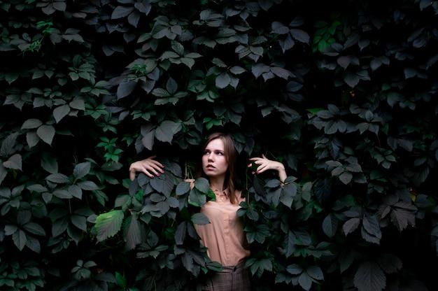 Jonge vrouw staat in groene bladeren alleen met de natuur, een vrouw raakt planten en dromen aan, een concept van een man in de natuur