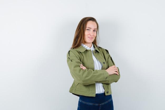 Jonge vrouw staat met gekruiste armen in shirt, jas en ziet er zelfverzekerd uit. vooraanzicht.