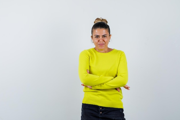 Jonge vrouw staat met gekruiste armen in trui, spijkerrok en ziet er zelfverzekerd uit