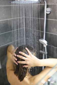 Jonge vrouw staat met haar rug onder een regendouche en wast haar haren