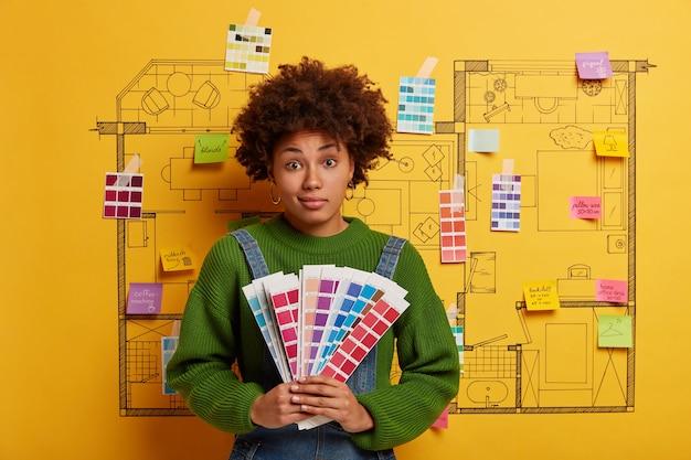 Jonge vrouw staat naast de schets van het huisontwerp klaar voor renovatie