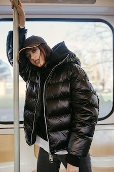 Jonge vrouw staat op de achtergrond van een raam in het openbaar vervoer