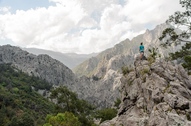 Jonge vrouw staat op de top van de berg