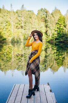 Jonge vrouw staat op een brug over een meer met een herfstlandschap. tonen.
