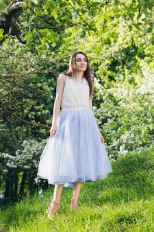 Jonge vrouw staat op een heuvel tegen de achtergrond van bloeiende bomen