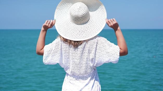 Jonge vrouw staat op zand in de buurt van zee en houdt een witte hoed vast