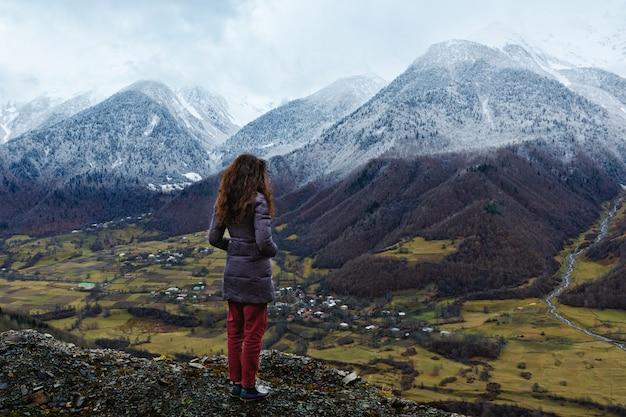 Jonge vrouw staat over een klif en kijkt naar met sneeuw bedekte bergen. georgië
