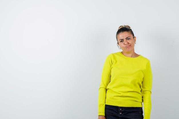 Jonge vrouw staat rechtop, grimast en poseert voor de camera in gele trui en zwarte broek en ziet er serieus uit?