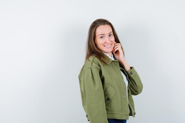 Jonge vrouw staat terwijl ze in shirt poseert en er charmant uitziet. vooraanzicht.