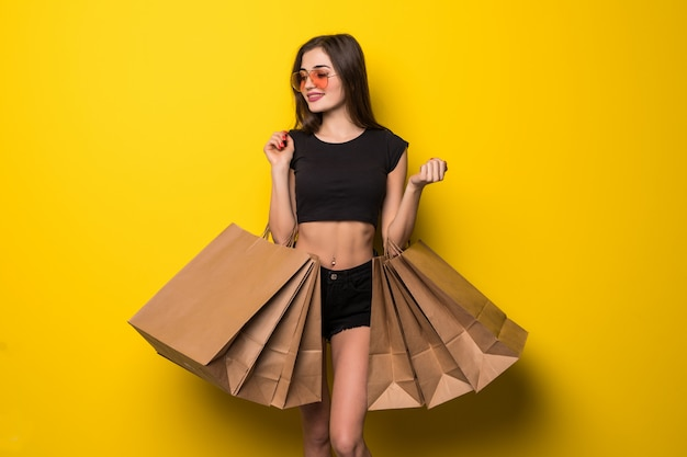 Jonge vrouw status geïsoleerd over gele muurholding het winkelen zakken
