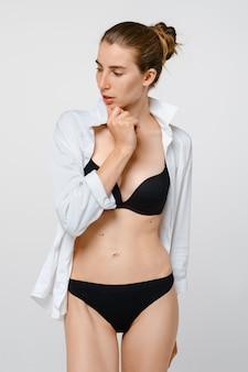Jonge vrouw steunt kin met haar hand in casual zwarte lingerie en wit overhemd
