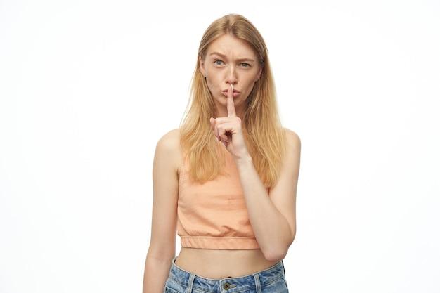 Jonge vrouw stilte gebaar tonen en houdt haar wenkbrauw omhoog, kijkt verward en boos