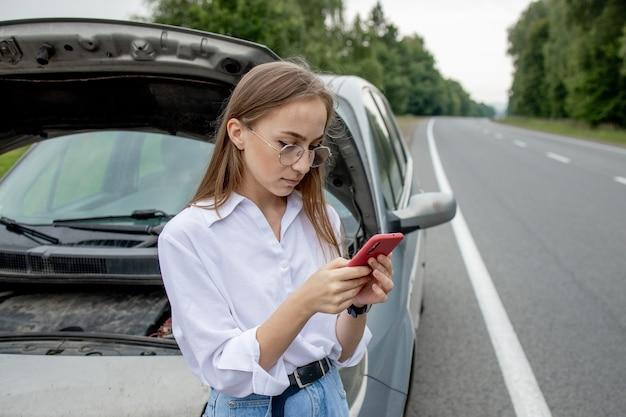 Jonge vrouw stond in de buurt van kapotte auto met opgedoken motorkap problemen met haar voertuig
