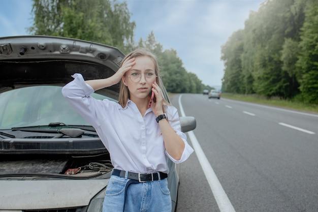 Jonge vrouw stond in de buurt van kapotte auto met opgedoken motorkap problemen met haar voertuig.