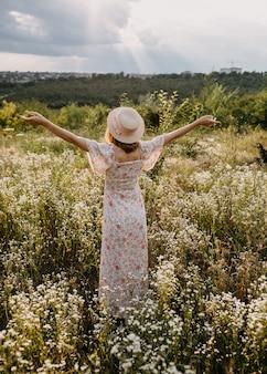 Jonge vrouw stond in een veld met wilde bloemen, met armen wijd open