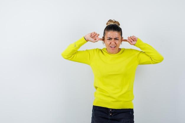 Jonge vrouw stopt oren met vingers in trui, spijkerrok en ziet er verward uit