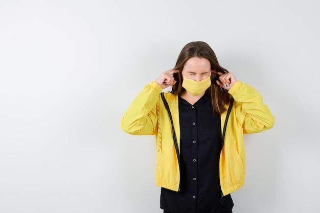 Jonge vrouw stopt oren met wijsvingers en kijkt gehaast