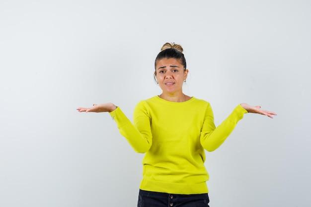 Jonge vrouw strekt haar handen op vragende wijze uit in gele trui en zwarte broek en kijkt verbaasd and