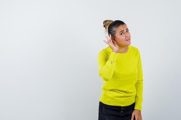 Jonge vrouw strekt haar handen uit in ondervraging, hand in hand in de buurt van het oor om iets te horen in een gele trui en zwarte broek en er gefocust uit te zien