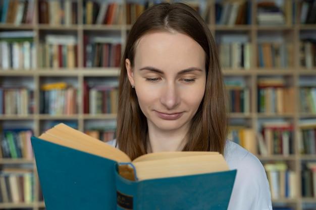 Jonge vrouw student die een boek in een bibliotheek leest