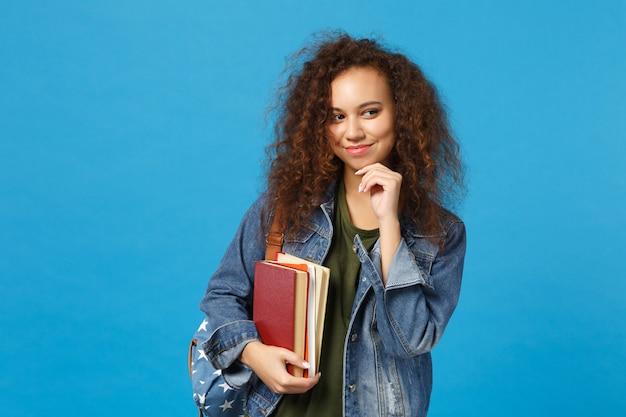 Jonge vrouw student in denim kleding en rugzak houdt boeken geïsoleerd op blauwe muur