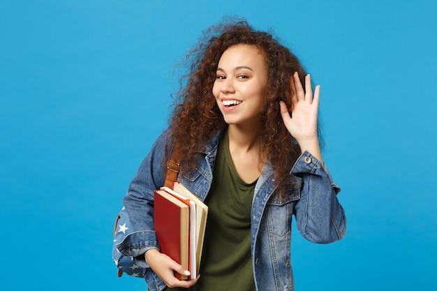 Jonge vrouw student in denim kleding en rugzak houdt boeken vast en probeert je te horen geïsoleerd op een blauwe achtergrond studio portret
